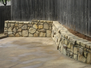 Rock retaining wall with privacy fence in Dallas, Texas home.